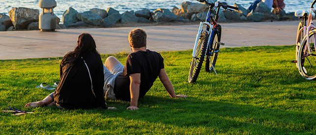 2 people sitting by the lake